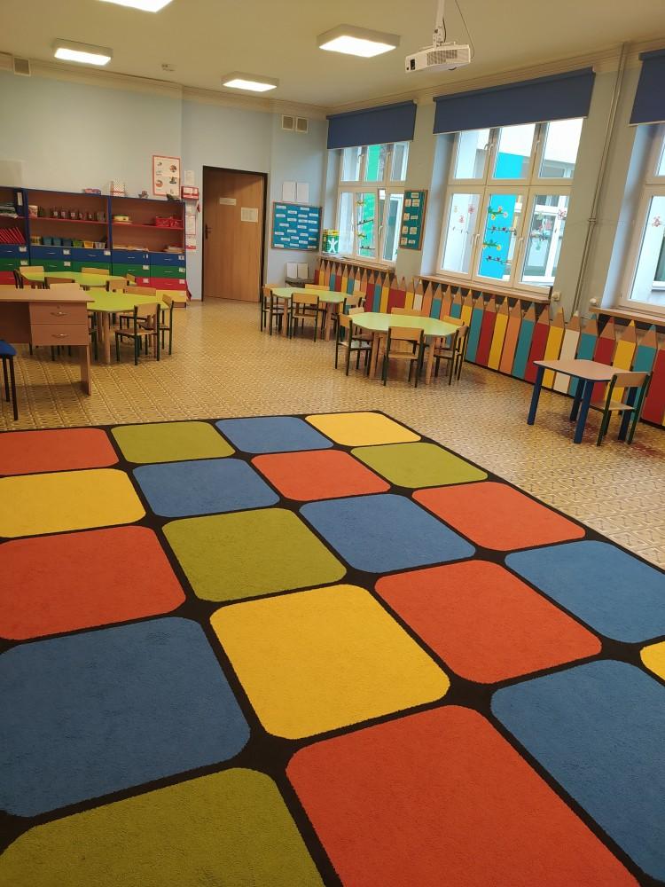Zdjęcie przedstawia stoliki przedszkolne, półki indywidualne, meble z przyborami plastycznymi i kolorowy dywan.