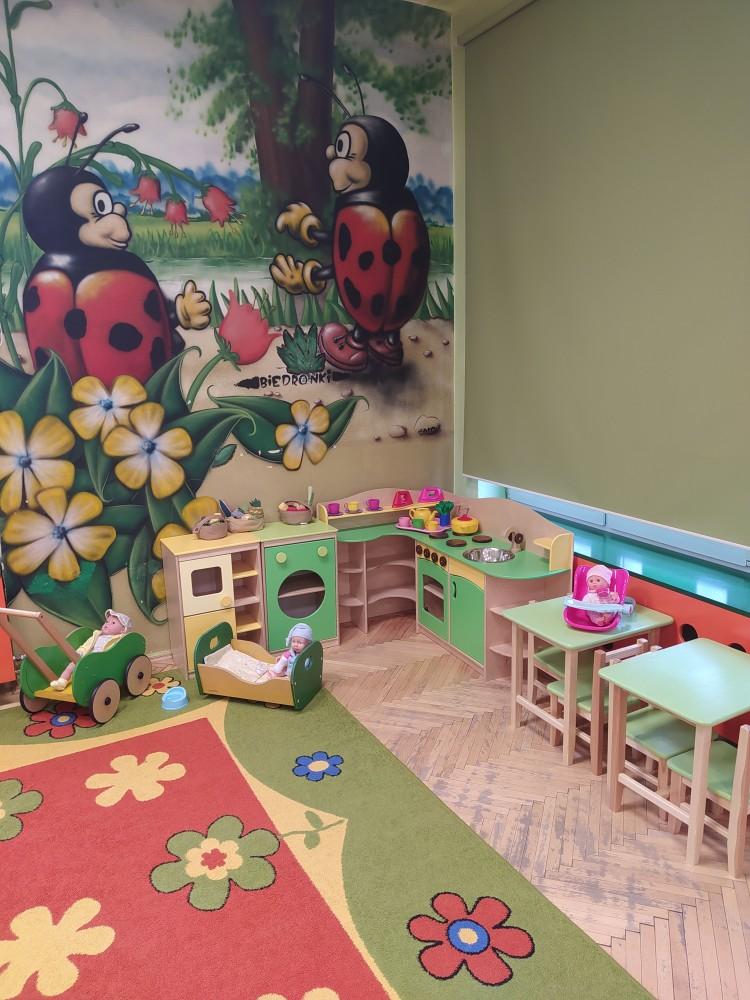 Zdjęcie przedstawia ścianę z graffiti przedstawiającym biedronki oraz kącik kuchenny.