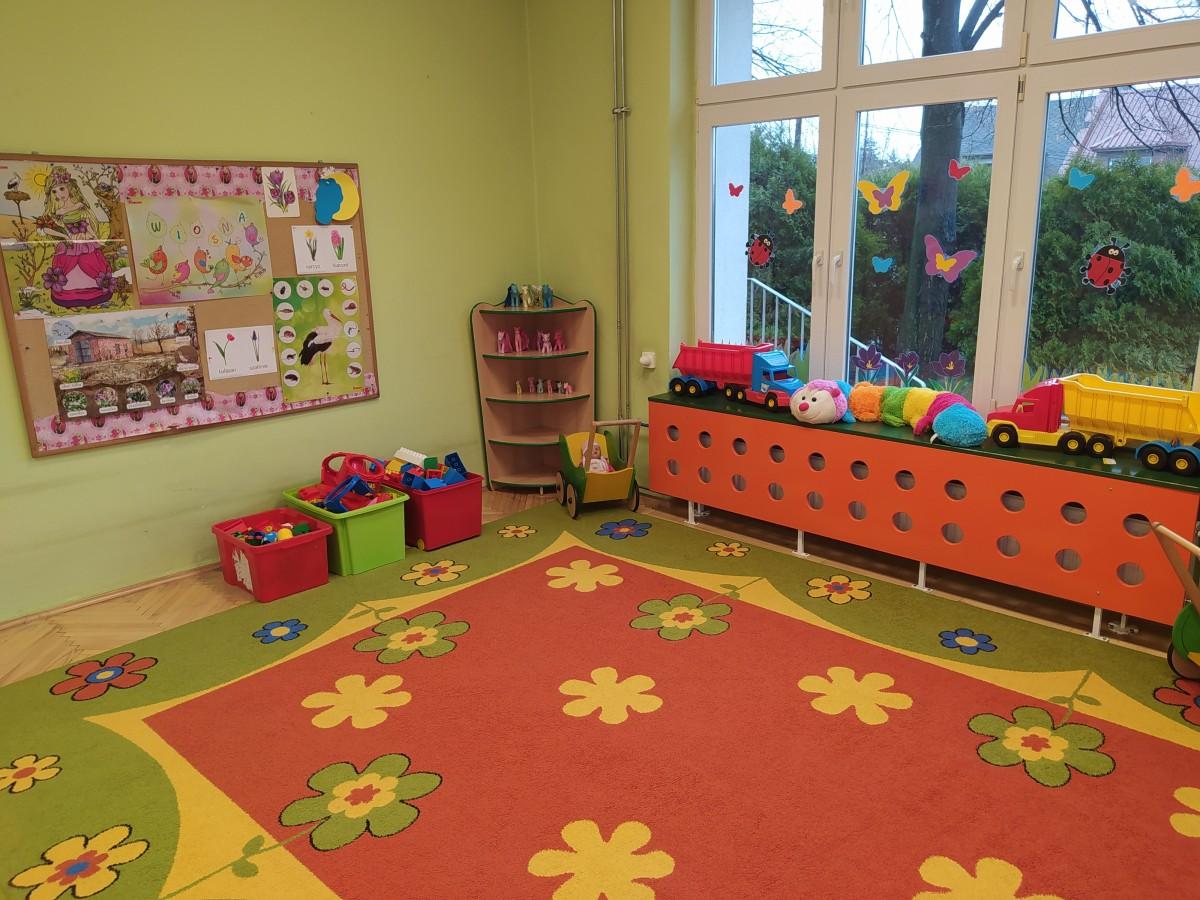 Zdjęcie przedstawia dywan w kwiaty, kącik zabawek i gazetkę tematyczną.