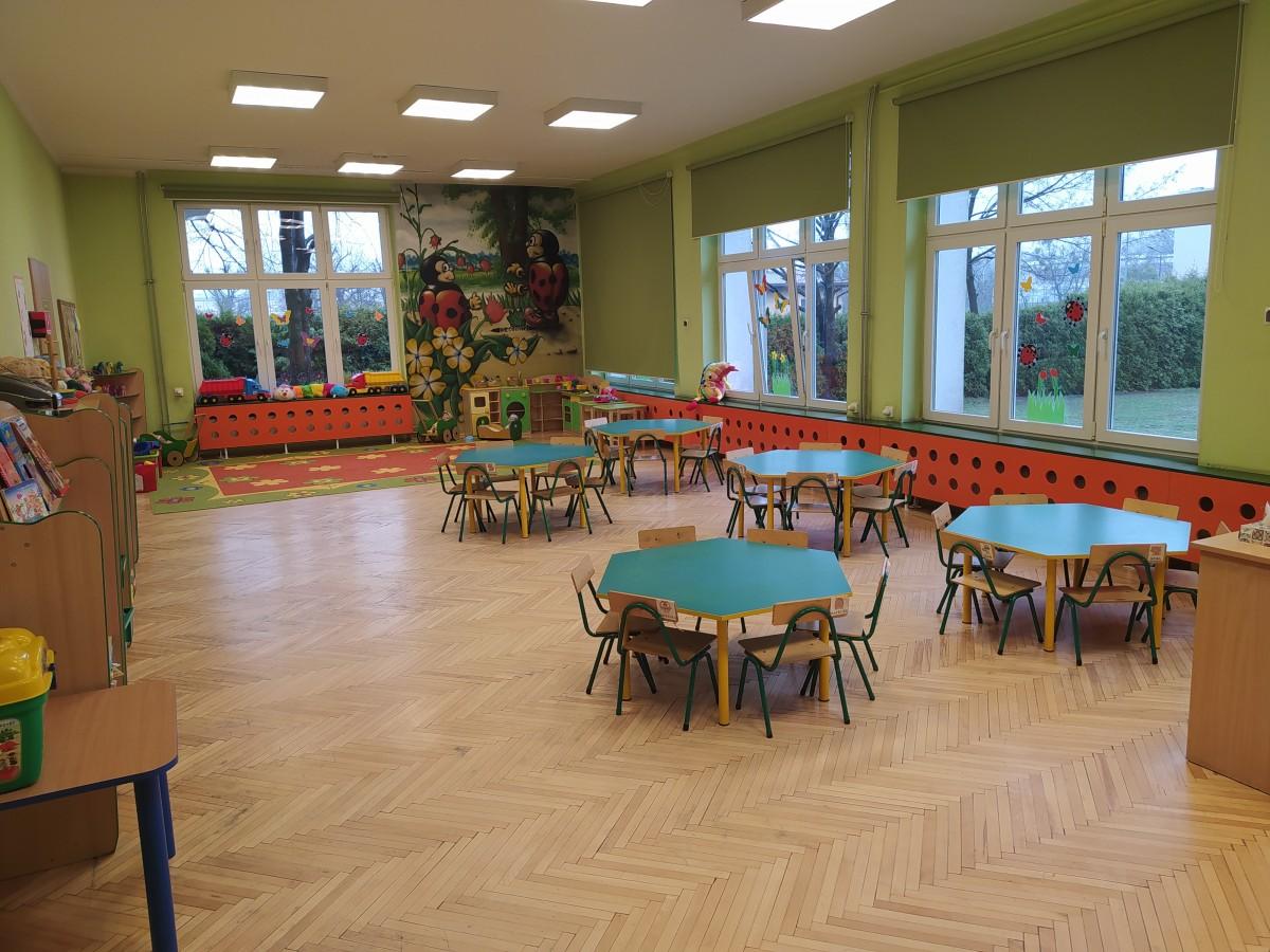 Zdjęcie przedstawia całą salę - stoliki, zabawki i kącik kuchenny.