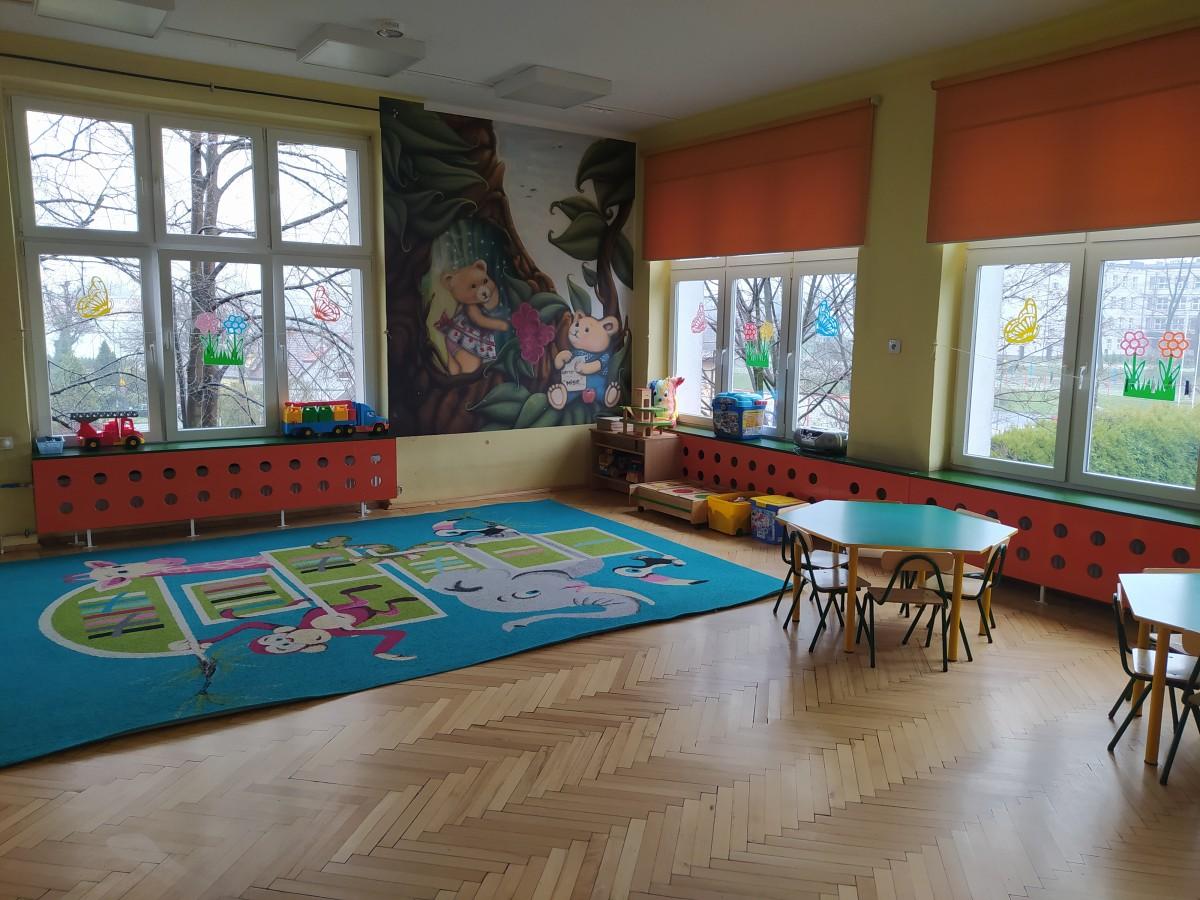 """Zdjęcie przedstawia salę grupy """"Misie""""- dywan, stoliki i zabawki."""