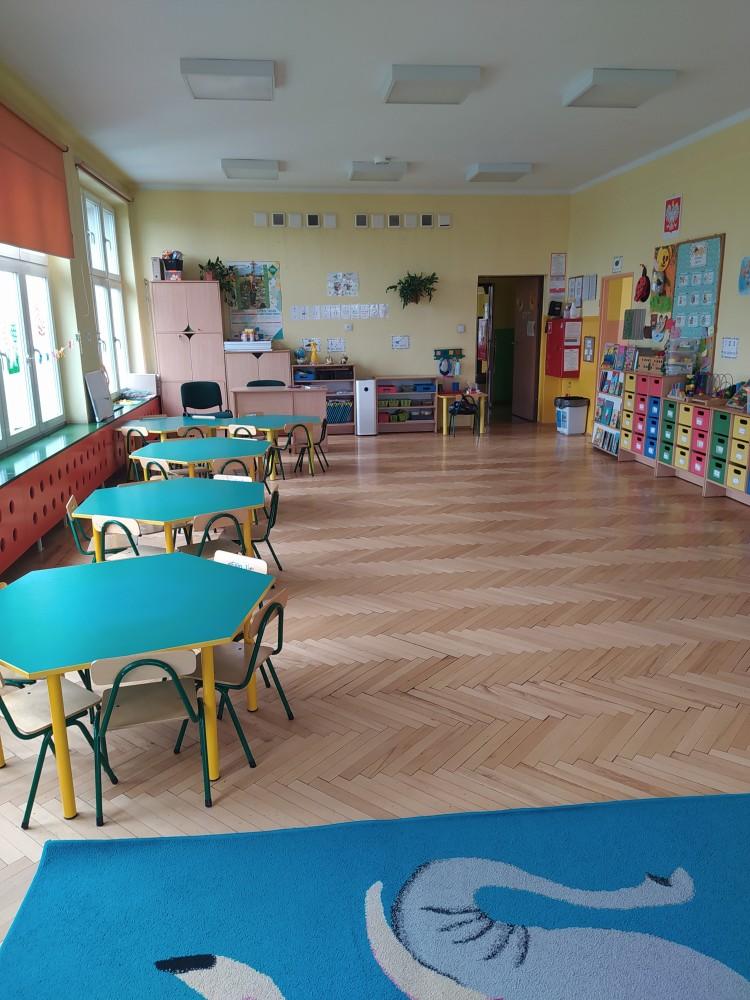 Zdjęcie przedstawia stolik, półki indywidualne dla dzieci i dywan.