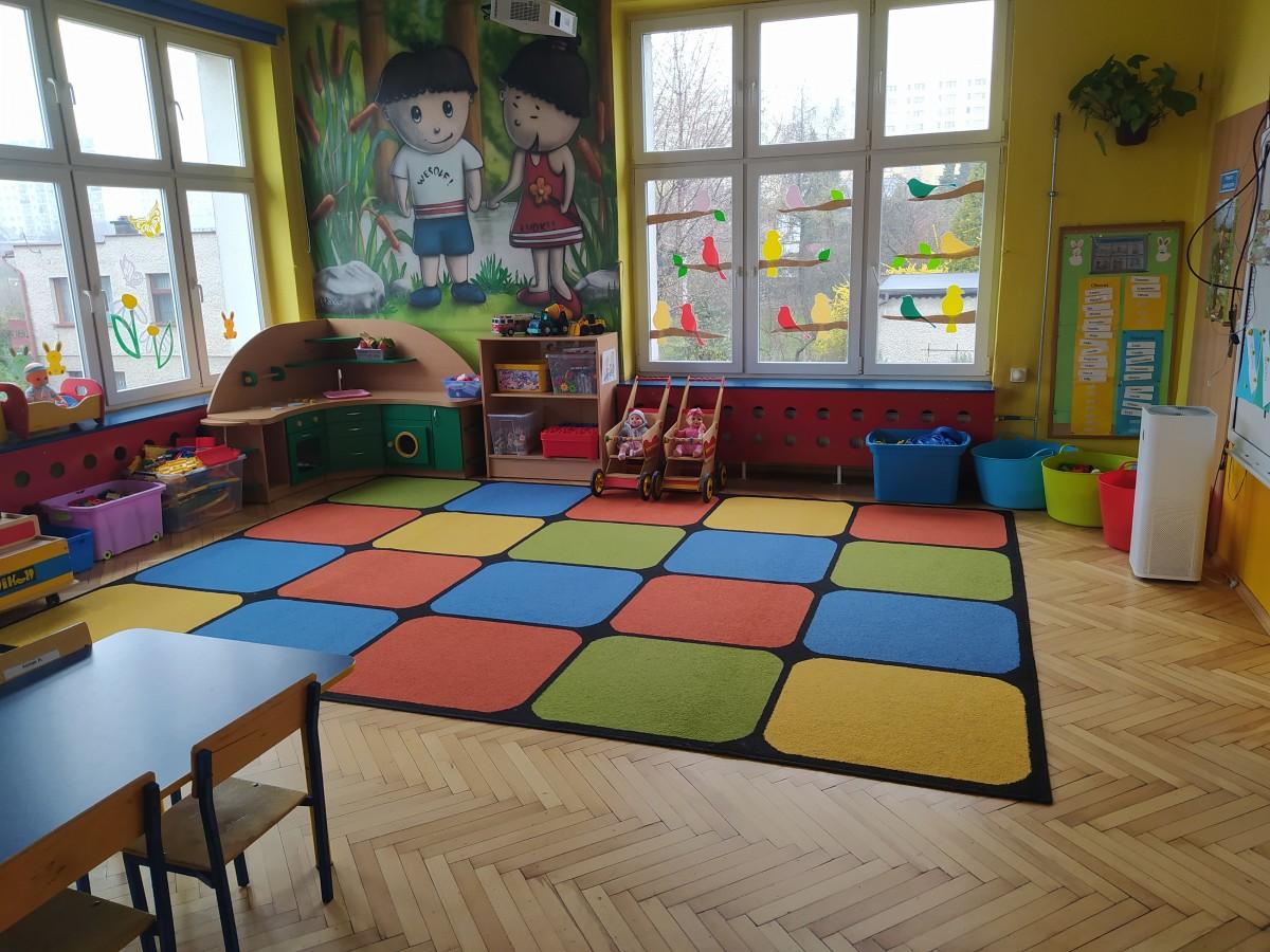 """Zdjęcie przedstawia salę grupy """"Wesołe Ludki"""" - kącik kuchenny, zabawki i kolorowy dywan."""