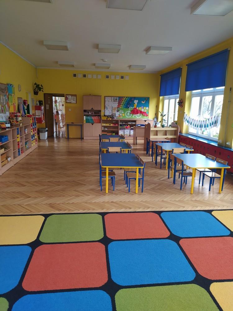 Zdjęcie przedstawia stoliki, kolorowy dywan, półki indywidualne dla dzieci oraz gazetkę z pracami dzieci.