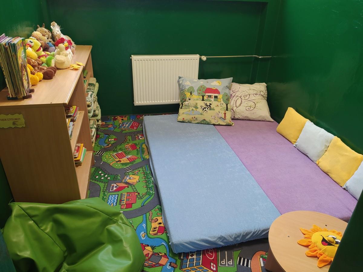 Zdjęcie przedstawia kącik wyciszeń w grupie Wesołe Ludki - materace, poduszki i półki z książkami.
