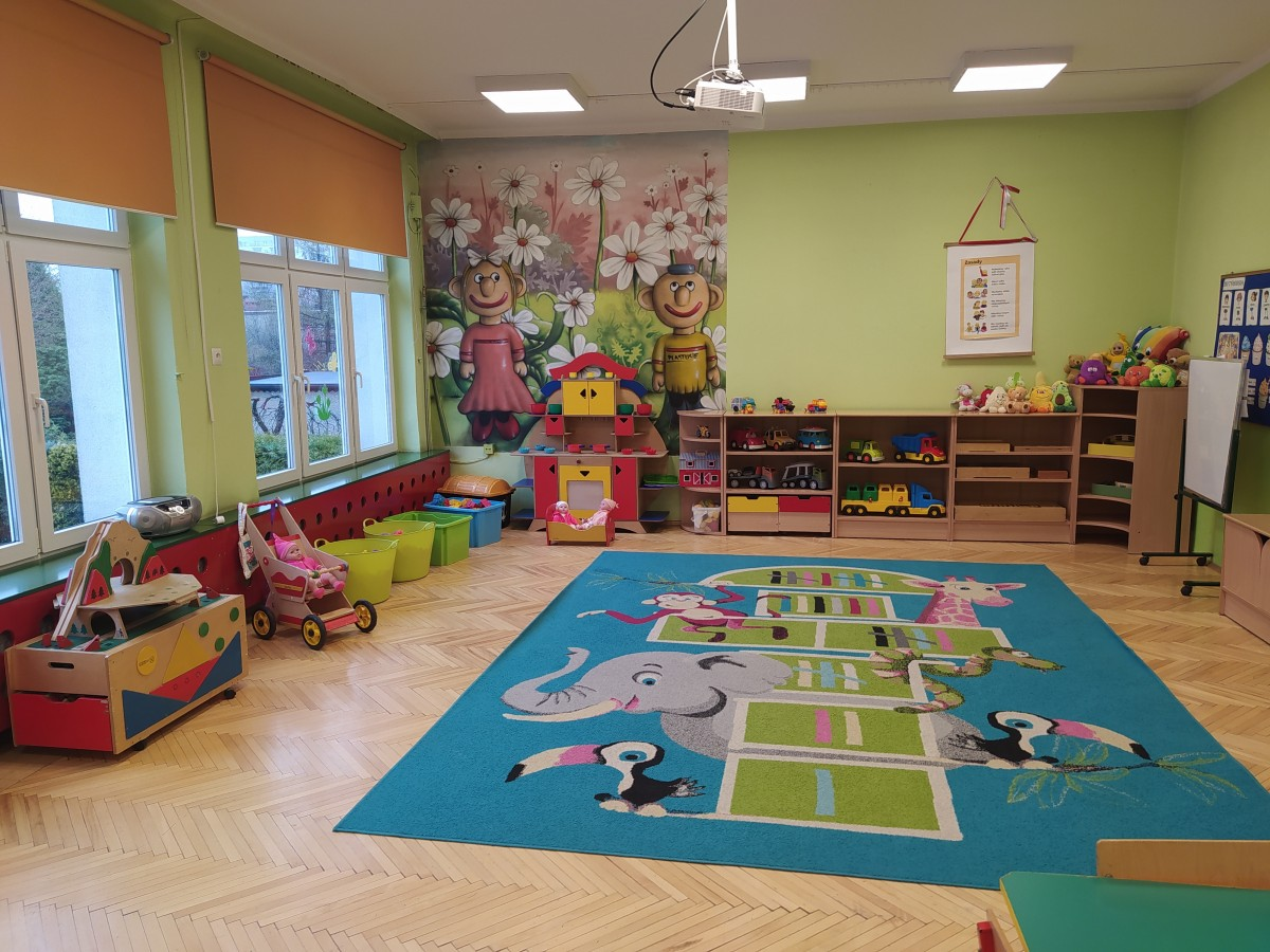"""Zdjęcie przedstawia salę grupy """"Plastusie""""- kącik kuchenny, zabawki, kolorowy dywan i graffiti na ścianie."""