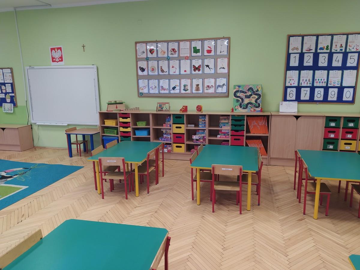 Zdjęcie przedstawia stoliki przedszkolne, półki z pomocami dydaktycznymi, półki indywidualne oraz tablicę multimedialną.