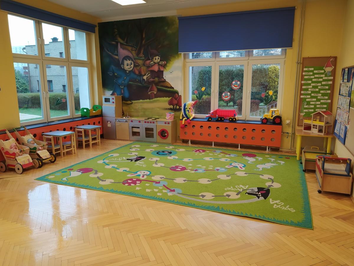 """Zdjęcie przedstawia salę grupy """"Krasnoludki"""" - kącik kuchenny, zabawki i kolorowy dywan."""