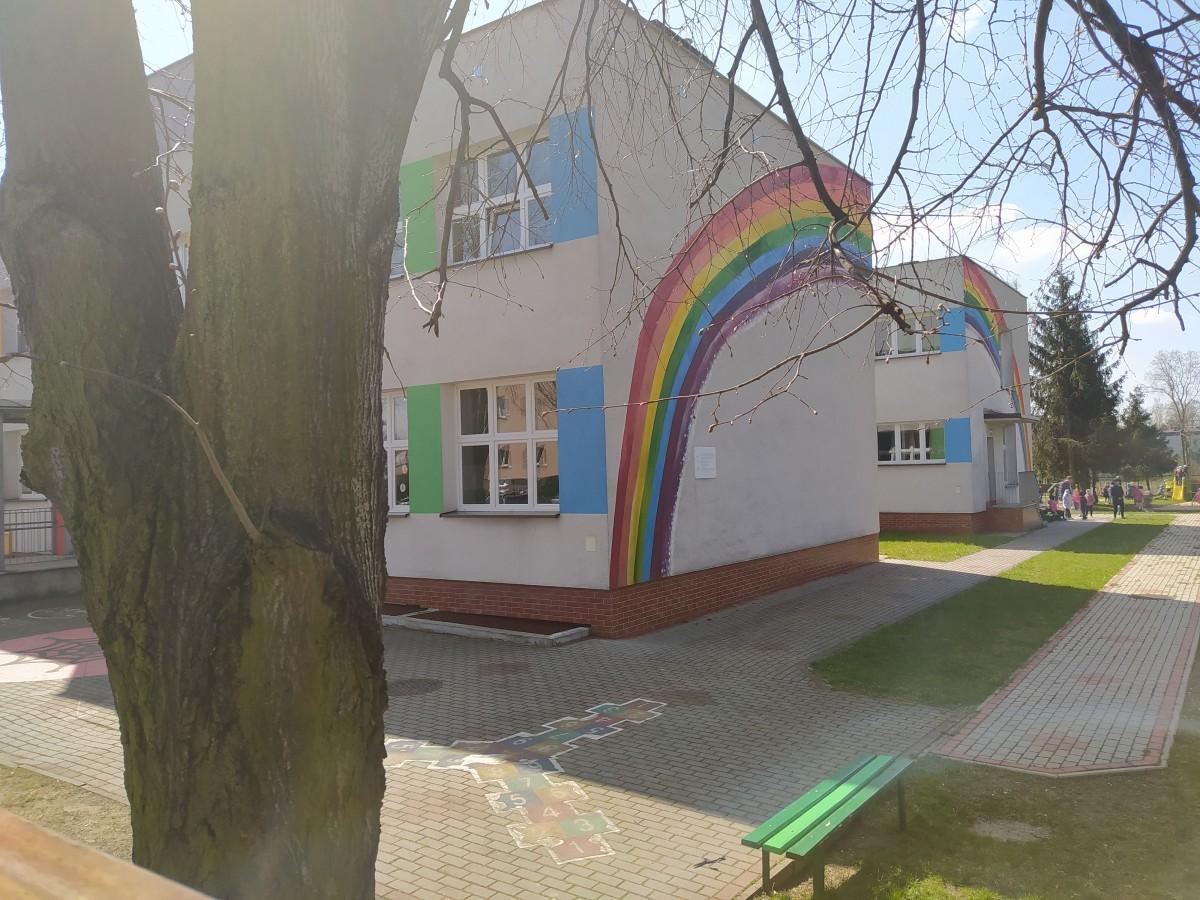 Zdjęcie przedstawia budynek przedszkola z kolorową tęczą.