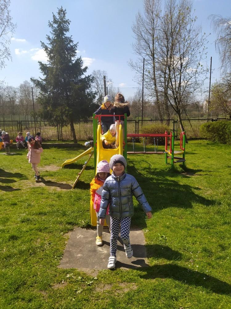 Zdjęcie przedstawia dzieci bawiące się na ogrodzie.